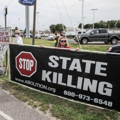 Mielenosoittajia, joilla on kuolemanrangaistusta vastustavia kylttejä.