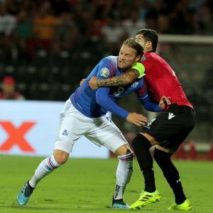 Birkir Bjanason stångas om bollen i en match mot Albanien.