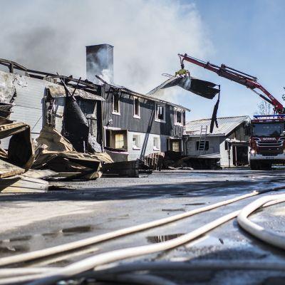 Palokunta raivaa Pöntiön lihatuotteen palavan tuotantorakennuksen kattoa.