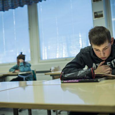 Seiskaluokkalainen lukee kirjaa äidinkielen tunnilla.