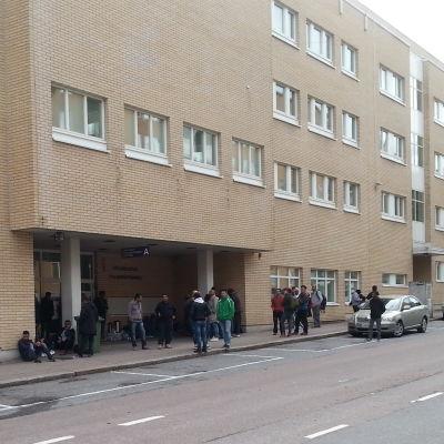Ett gäng asylsökande utanför polisstationen i Åbo.