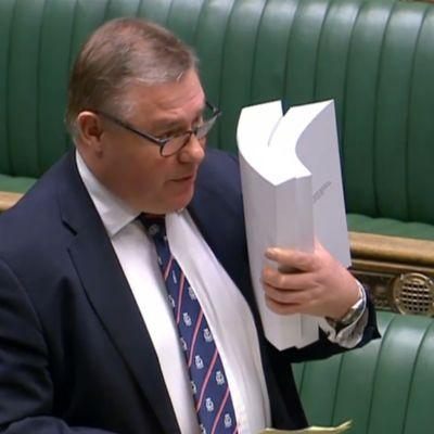 Den konservativa parlamentsledamoten Mark Francois håller en kopia av handelsavtalet medan han deltar i debatten om underhuset den 30 december 2020.