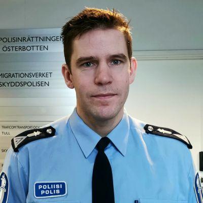 En man i polisuniform står intill en vit vägg. På väggen finns ett plakat med texten polisinrättningen i Österbotten.