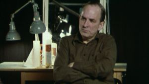 Närbild på Ingmar Bergman som sitter på en stol framför en spegel.