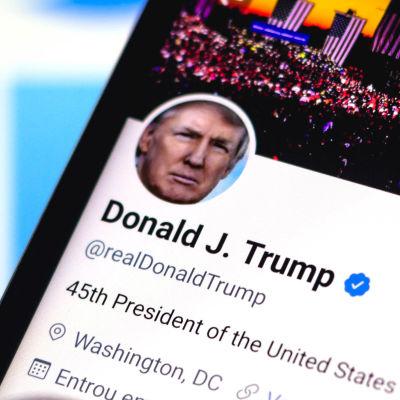 Donald Trumps Twitterkonto i förgrunden, flera varianter av Twitters logga i bakgrunden.