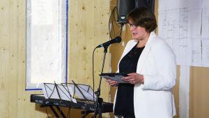 En medelålders kvinna i vit kavaj står framför en mikrofon och läser från någonting.
