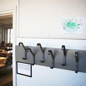 Tyhjä käytävä Ilmaristen yhtenäiskoulussa Liedossa. Seinällä oppilaan piirustus koronaviruksessta.