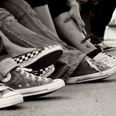 Ungdomars skor på svartvit bild.