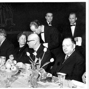 Vid middagsbordet på Kekkonens vänstra sida Sovjetestlands partiledare Johannes (Ivan) Käbin. På Kekkonens högra sida Käbins ingermanländska hustru Toini-Inkeri Käbin