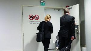 Kvinna och man fotad bakifrån som går genom en dörr.