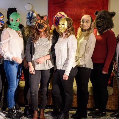 Tio luciakandidater i bild med mask framför ansiktet.