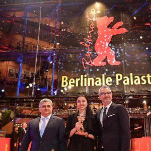 Näyttelijätär Baran Rasoulof, tuottajat Farzad Pak ja Kaveh Farnam poseeraavat Kultaisen karhun kanssa Berliinissä.