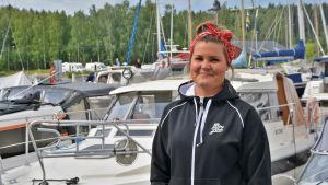 En ung kvinna i svart luvtröja står framför flera båtar. Hon tittar in i kameran och ler.