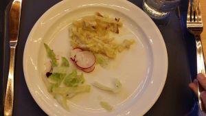 4-luokkalaisen tytön lounasannos: vähän broilerikiusausta, salaattia, retiisiä ja lasi vettä