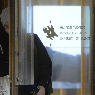 Studerande som går ut genom dörren vid Helsingfors universitet.