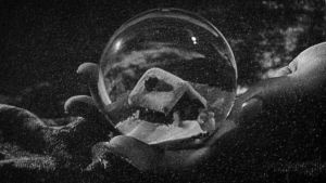 """Käsi pitelee lasista """"lumisadepalloa"""", jonka sisällä on pieni mökki talvimaisemassa. Kuva elokuvasta Kansalainen Kane."""