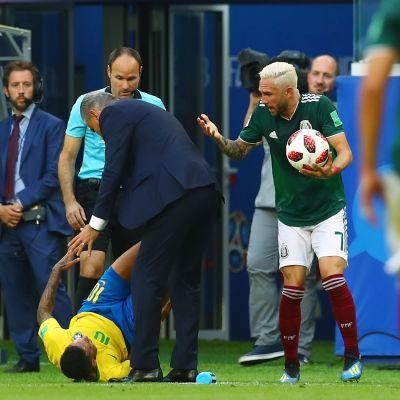 Neymar ligger i gräset, Miguel Layun står med bollen i handen.