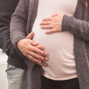 Miehen ja naisen kädet naisen raskausvatsan päällä.