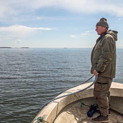 Micke Lindholm seisoo veneensä nokassa.