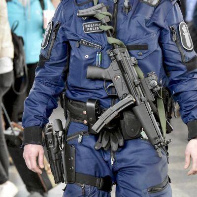 Poliisi partioi konepistooli esillä Helsinki-Vantaan lentoasemalla.