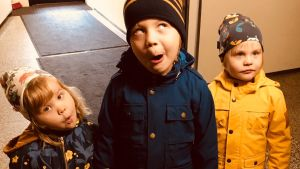 Kolme lasta ilveilevät kameralle ulkovaatteissaan.