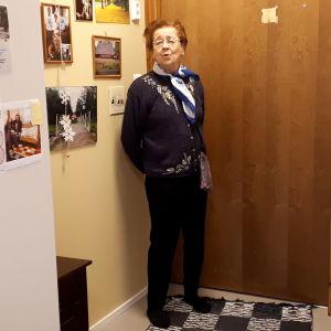vanha nainen on huoneensa ovella hoivakodissa