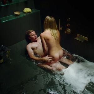 Ett par har sex i ett stort lyxigt, skummande badkar.