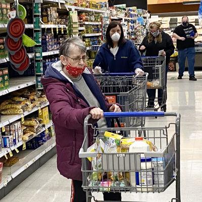 Maskeilla suojautuneita ihmisiä ruokakaupassa Monroessa, Michiganissa