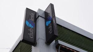 På bilden syns två skyltar i hörnet av en byggnad. På båda skyltarna står det club alexia.