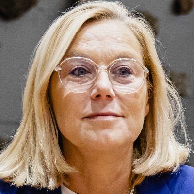 En kvinna i glasögon och blont hår sitter vid ett bord. Hon tittar åt sidan.