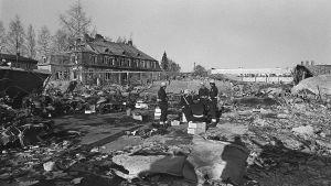 Lapuan patruunatehtaan räjähdyksen raunioita 13.4.1976. Pelastusmiehet istuvat patruunalaatikoilla onnettomuuspaikalla.