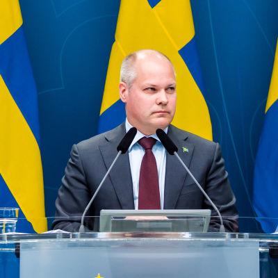 Morgan Johansson med Sveriges flaggor i bakgrunden.