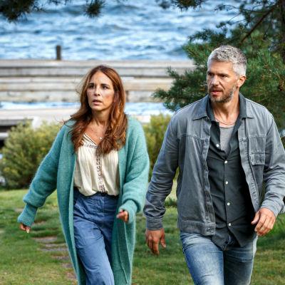 Nora och Alexander kommer sammanbitna gåedne över en gräsplan.