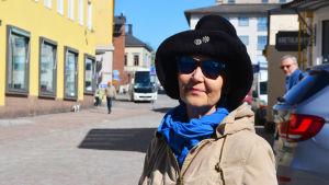 En dam i hatt och solglasögon står i Gamla stan i Borgå.