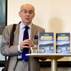 Jukka Tarkka med två exemplar av sin nya Ålandsbok.