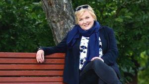 En kvinna sitter på en parkbänk. Glad. Grönska, i bakgrunden en trädstamm.