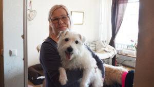 En medelålders kvinna står inne i en lägenhet. Hon håller en vit hund i famnen och båda tittar in i kameran.