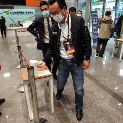 Vierailijat desinfioivat käsiään saapuessaan Tapein kansaivälisille matkailumessuille lokakuussa 2020.