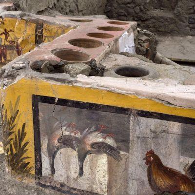 Monivärisesti ja taidokkaasti koristeltu katukeittiön tiski Pompeijissa.