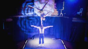 Sirkustaiteilijapari, nainen seisoo yhdellä kädellä miehen pään päällä.