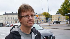 En man i svart jacka står ute på en gata i centrala Lovisa.