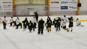 Ett ishockeylag har samlats på isen runt sin tränare som pekar på en skrivtavla.