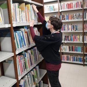 Nainen täyttää kirjahyllyä kirjastossa.