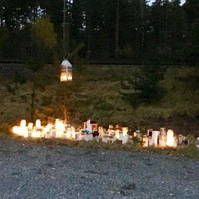 Många ljus brinner på marken vid en plankorsning till minne för fyra personer som avled i en olycka i slutet av oktober 2017.