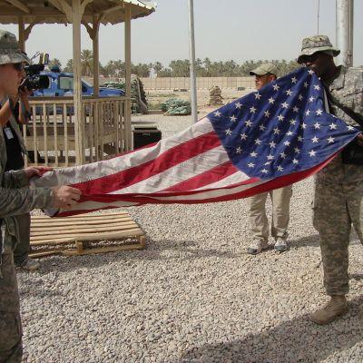 Amerikanska soldater viker ihop USA:s flagga i Irak.