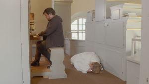 Helene vilar på golvet medan Thomas arbetar som kantor
