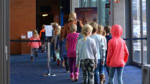 Flera barn och en vuxen på väg in i en biosalong.