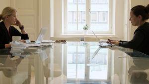 Karriärkvinnorna vid ett stort, blankt förhandlingsbord.