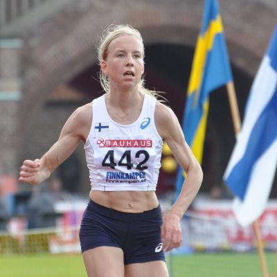 Löpare går i mål framför Sveriges och Finlands flaggor,
