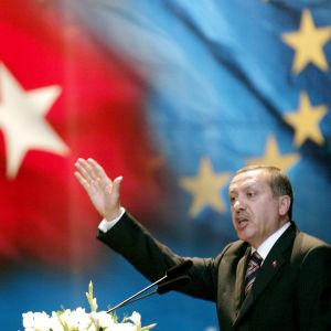 Recep Tayyip Erdogan Turkin ja EU:n lippuja vasten.